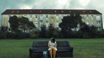 a photo of a young woman sitting on a sofa with a suitcase in front of a large housing complex