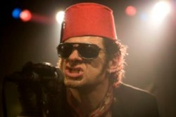 Photo of a man wearing a red fez. He's got sunglasses on too. It is Andy Serkis's face.