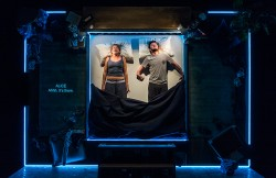A photograph from the play The Solid Life of Sugar Water. Actors Genevieve Barr (Alice) and Arthur Hughes (Phil) stand in a vertical bed which has neon lighting around it. Alice is grimacing.