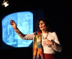photo of writer Lynne Blackwood performing against a black background, her hand raised forward in front of a blue projection of photographs