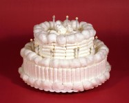 Many tampons and cotton wool balls are arranged in the form of a two-tiered white cake.