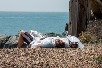 Two people in ponchos lie down on a pebbly beach as part of the interactive piece 'The Last Resort'.