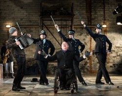 Garry Robson as JJ Peachum, King of the Beggars, leads a chorus of policemen in Graeae's touring production of The Threepenny Opera. The policemen pose with their truncheons held high against a stark stage set