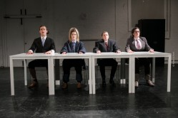 Promotional photograph for Silent Faces' show Follow Suit featuring the performers all sitting at desks in oversized suits pulling worried faces.