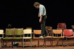 Photo of performer Jochem Stavenuiter walking across a row of chairs laid out across a stage