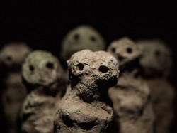 Three unfired clay figures representing individual stories of the cost of austerity