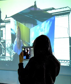 photo of a young woman standing in shadow in the foreground. She watches a film on an i-pad in front of a projection in the background