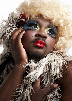 Le Gateau Chocolat poses in false eyelashes, glittering make-up and feathers, looking away from the camera