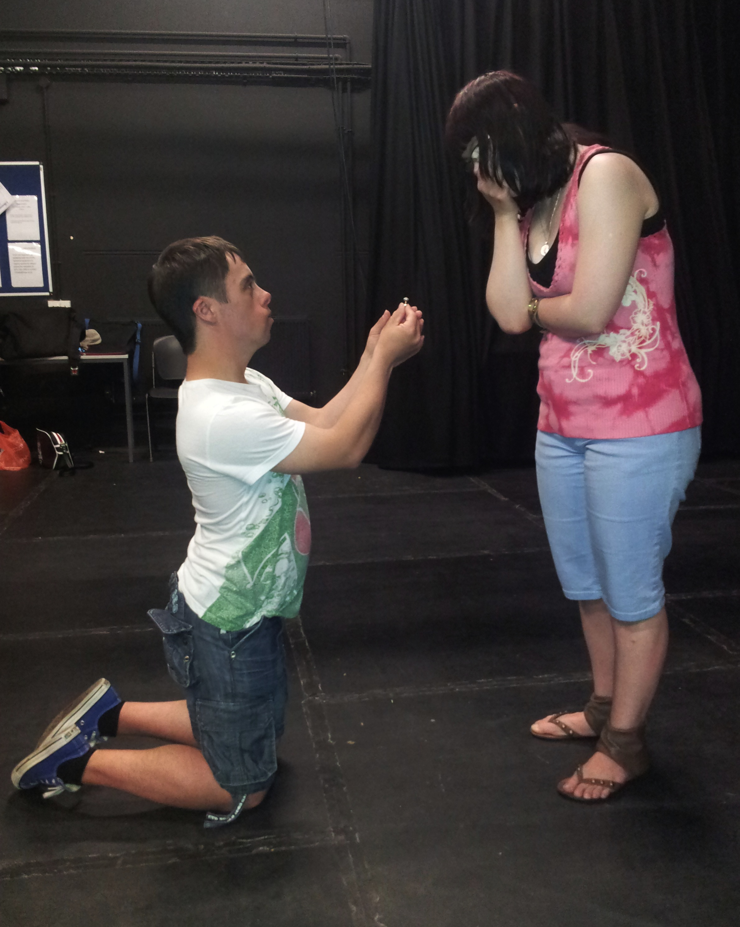 A kneeling man offers a ring to woman who holds her hands to her mouth in surprise